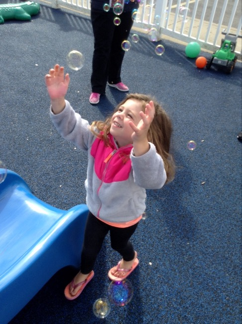 a child blowing bubbles at Syracuse daycare during recess