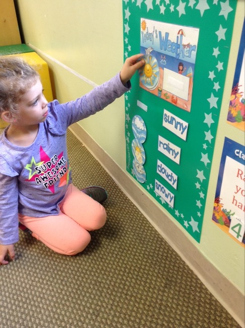 a child putting weather graphics on a school board during daycare